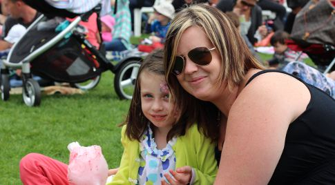 Mother and daughter sat on grass with candy floss