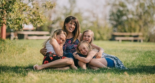 woman with 3 girls sitting in a field hugging