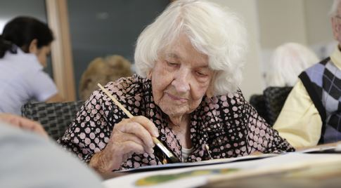 An elderly woman sat at a table painting with a paintbrush